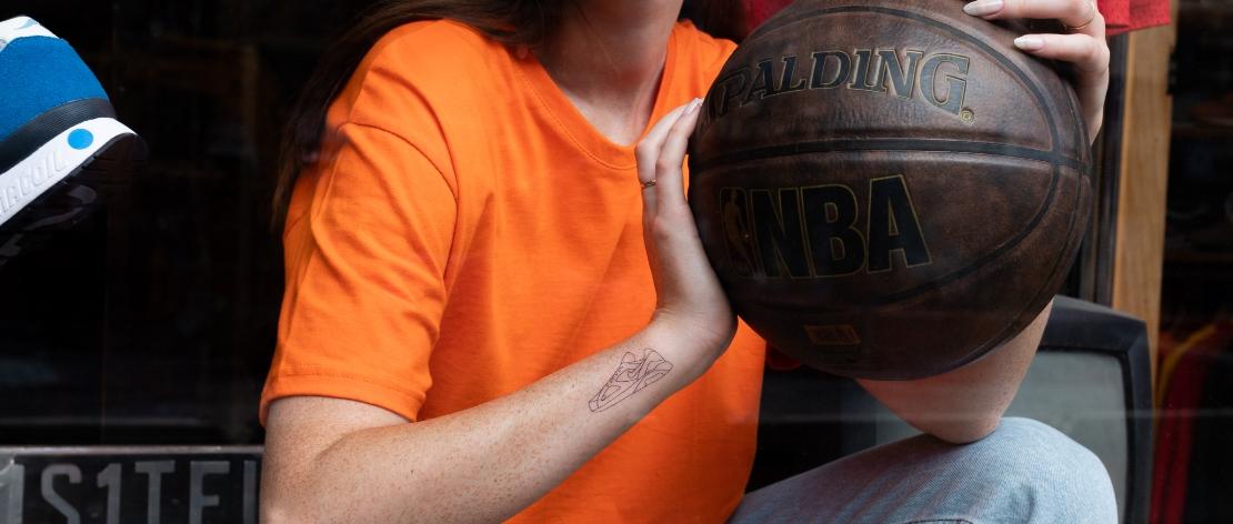 Femme avec un tatouage de sneaker sur le bras et tenant un balon de basket